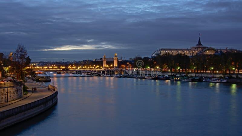 在河围网和`盛大Palais `的玻璃屋顶的Pont亚历山大III桥梁在巴黎在晚上里 库存图片