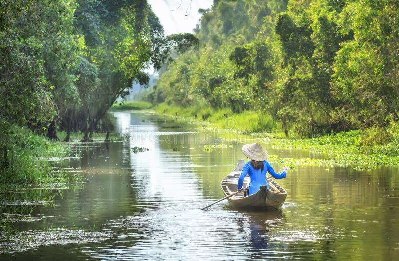 在河国家的妇女划船 免版税库存照片