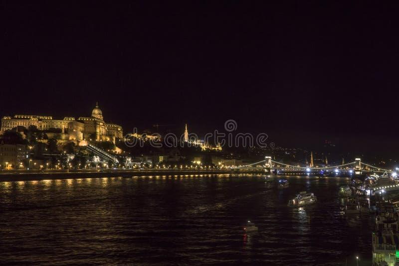 在河多瑙河的夜布达佩斯 布达城堡奥斯陆王宫和铁锁式桥梁在背景的塞切尼lanchid 匈牙利 图库摄影