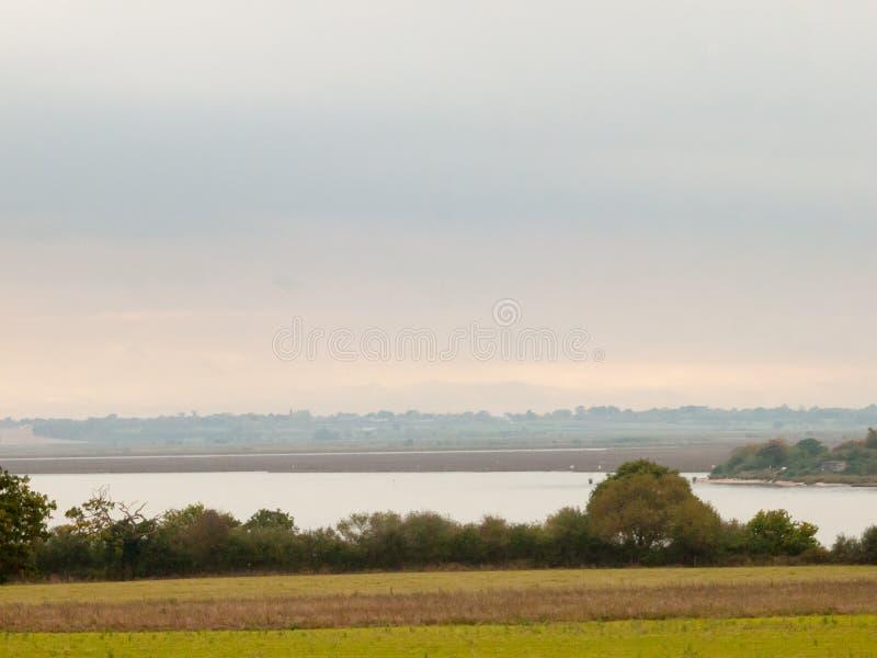 在河小河阴云密布秋天s前面的绿色领域风景 免版税库存图片