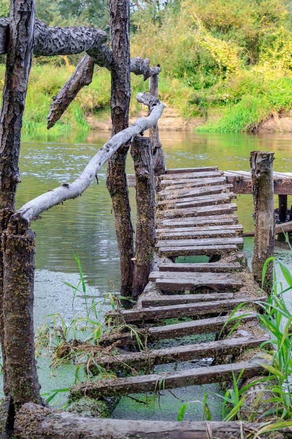 在河岸特写镜头的老木渔桥梁 河风景在晴朗的秋天早晨 免版税库存照片