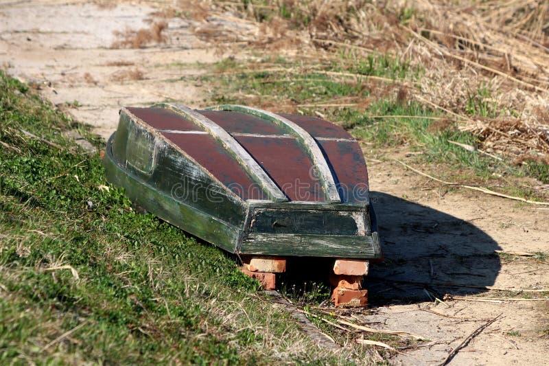 在河岸的具体部分的红砖上把放的葡萄酒土气老被翻转的河船围拢与未割减的草 免版税库存图片