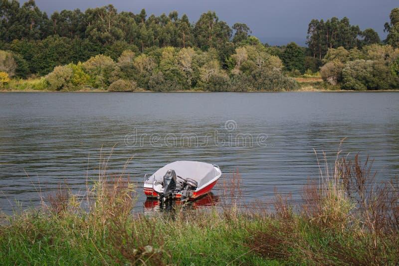 在河岸附近的汽船有在另一边的森林的 在湖的红色和白色小船在雷暴前 库存照片
