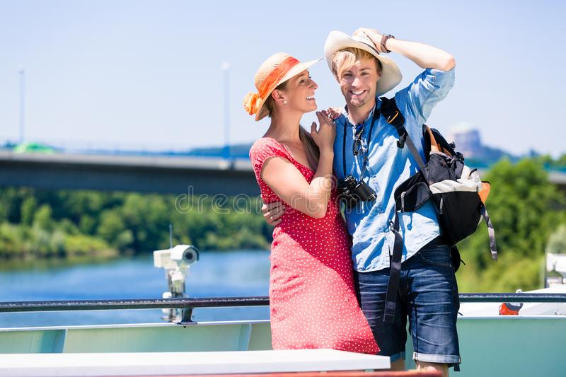 在河巡航佩带的太阳帽子的夫妇在夏天 免版税库存图片