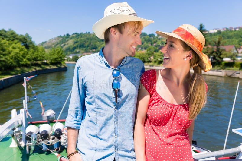 在河巡航佩带的太阳帽子的愉快的夫妇 免版税库存图片