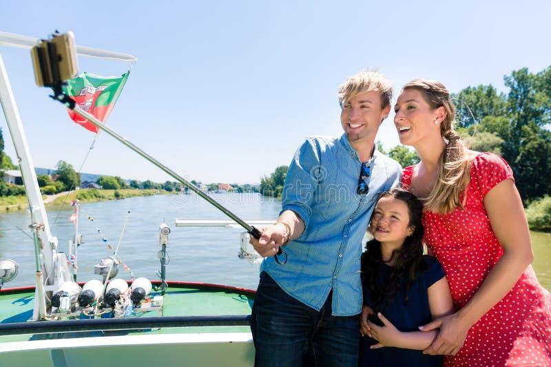 在河巡航的家庭用selfie棍子在夏天 免版税库存图片