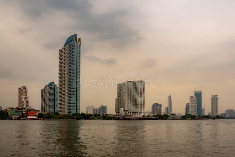 在河旁边的住宅,商务和企业大厦有阴暗天空的 库存照片