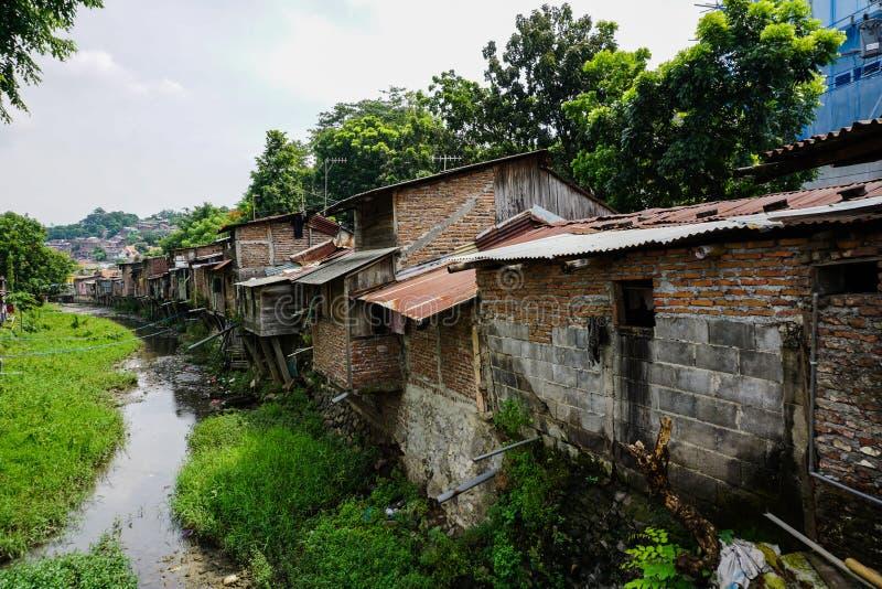 在河旁边的贫民窟有在三宝垄拍的灌木照片的印度尼西亚 库存图片