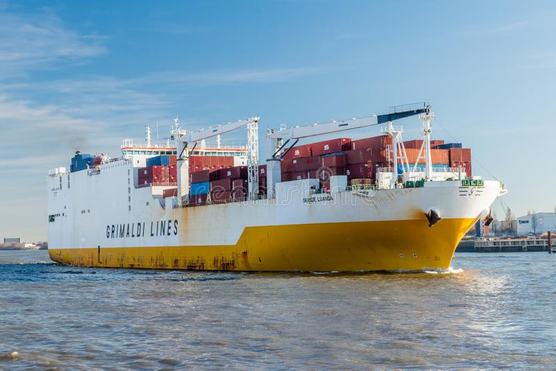在河易北河的重创的罗安达货船 格里马尔迪线船  免版税库存照片