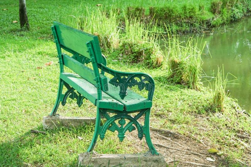 在河沿的绿色长凳 免版税库存图片
