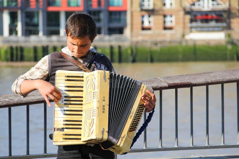 在河沿街道上的一部年轻卖艺人执行的手风琴在Sou 免版税库存图片