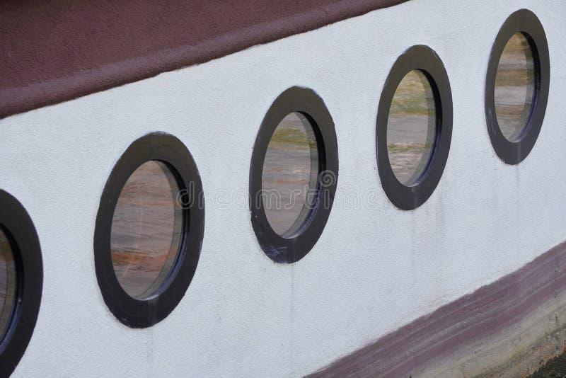 在河游船,舰上,水反射的圆的舷窗在窗口,老船里 免版税库存照片