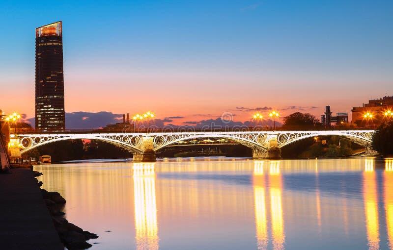 在河瓜达尔基维尔河日落的,塞维利亚,安达卢西亚,西班牙的特里亚纳桥梁 库存照片