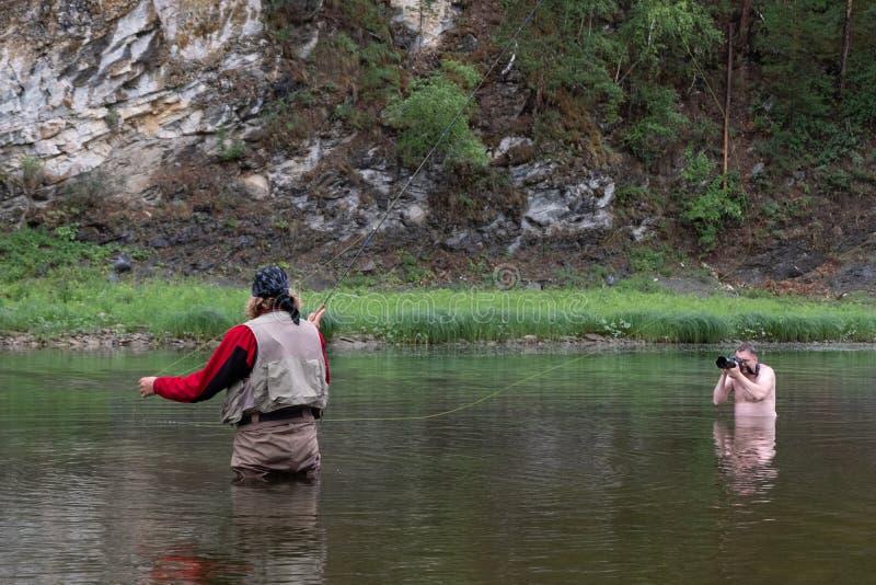 在河用假蝇钓鱼和不穿衣服的摄影师 报告文学 Photosession本质上 r 库存照片
