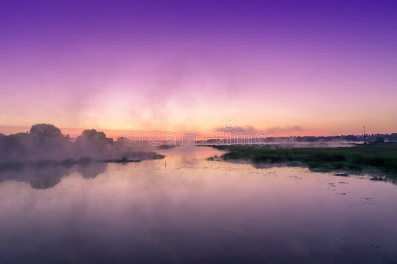 在河的不可思议的有薄雾的紫色日出 免版税库存图片