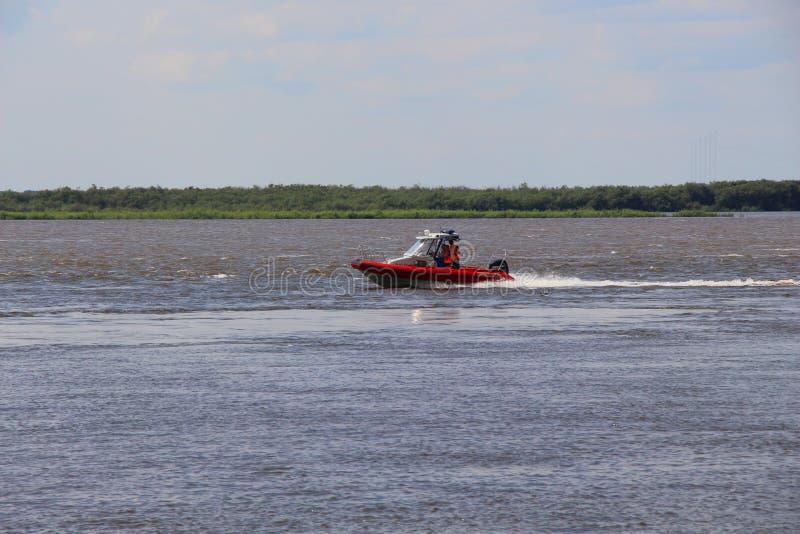 在河的小船反对天际/红色小船/ 免版税库存图片
