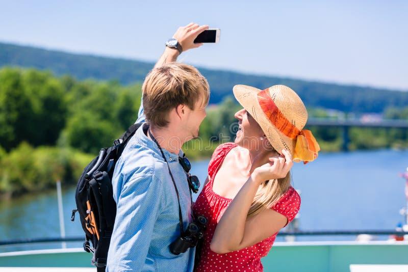 在河的年轻夫妇在采取selfie的夏天巡航 免版税图库摄影