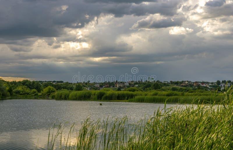 在河的日落天空,在背景中有教会的一个村庄 免版税图库摄影