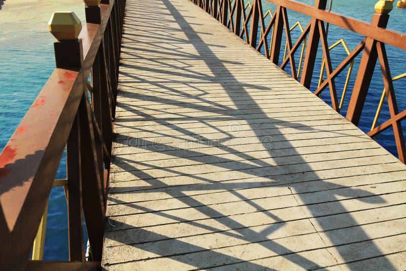 在河的桥梁公园水泥地板木路轨天空蔚蓝的反射在河下 免版税库存图片