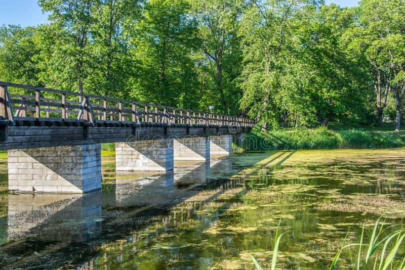 在河的桥梁在城市公园 在砖高跷的木桥 免版税库存图片