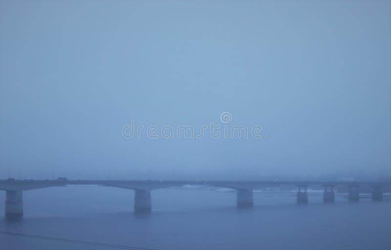 在河的桥梁在工业城市在雾期间的冬天 库存照片