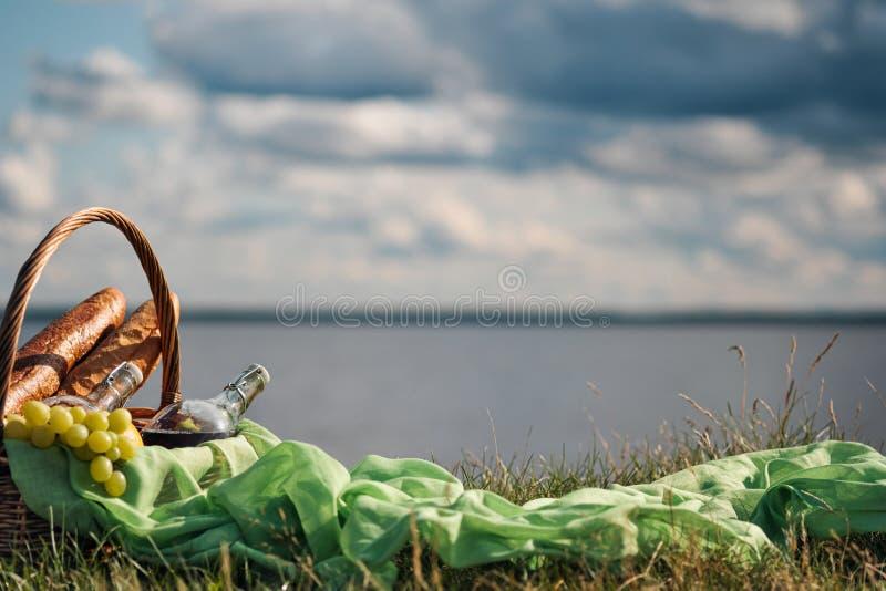 在河的河岸的野餐篮子反对天空的 好吃,面包,被装瓶的汁液 库存照片