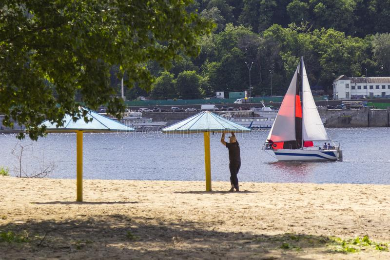 在河的游艇浮游物沿城市 一个人在海滩站立在从太阳的一把伞下 库存图片