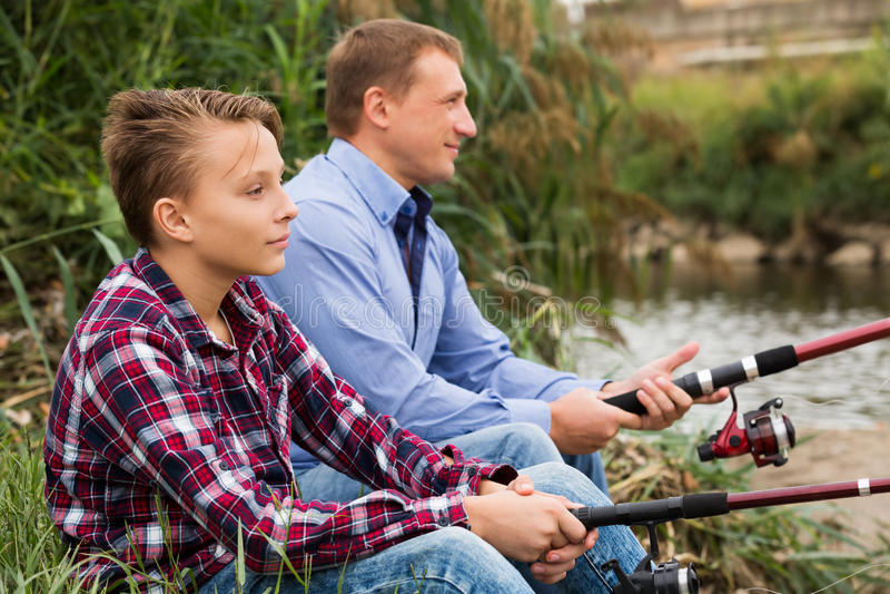 在河的父亲和儿子渔 免版税库存照片