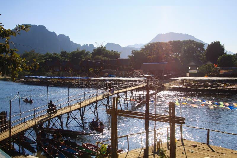 在河的狭窄的竹桥梁在深刻的晚上太阳的Vang Vieng,老挝微明下  免版税库存照片