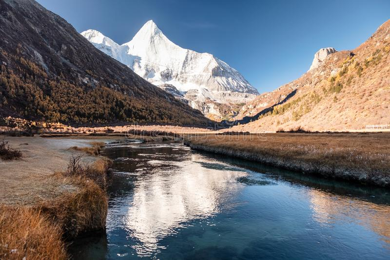 在河的神圣的雪山Yangmaiyong反射在高原的秋天谷的 库存图片