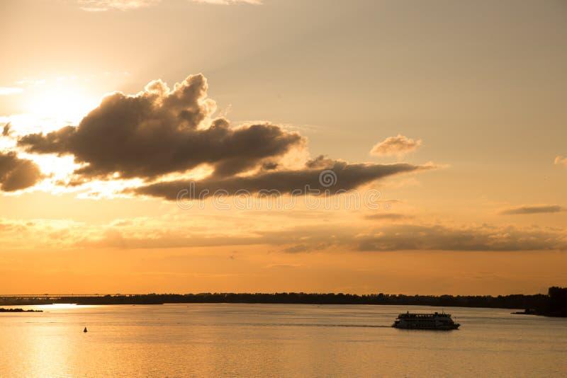 在河的美好的金黄日落 在日落期间,恋人采取小船乘驾 免版税库存照片