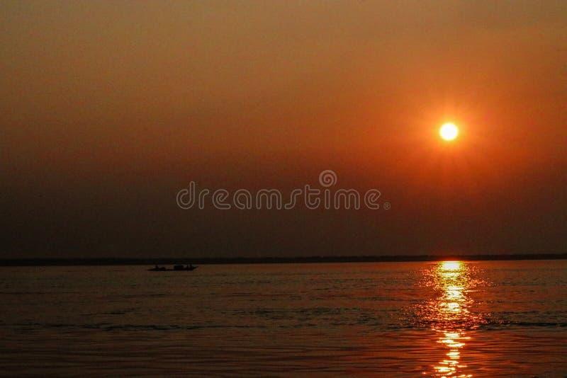 在河的美好的金黄橙色日落和经历的小船 免版税库存图片