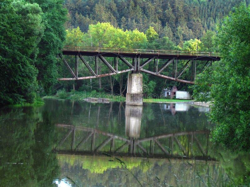在河的老铁路桥,反映在水中 免版税库存照片