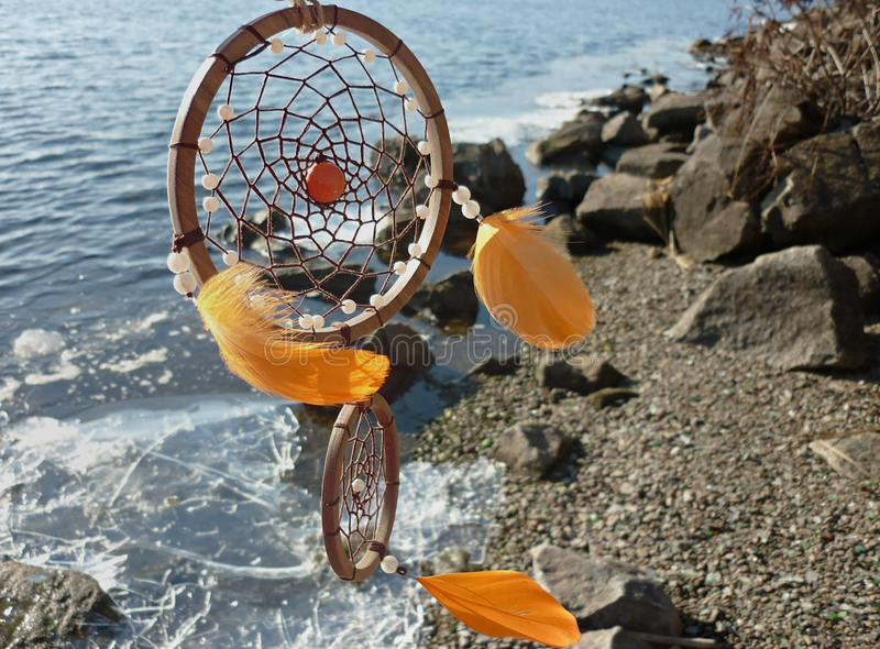 在河的背景的Dreamcatcher Dreamcatcher日落,山,boho别致,种族护身符,标志 库存照片