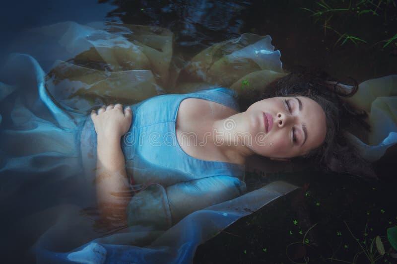 在河的蓝色礼服的年轻美丽的被淹没的妇女 免版税库存图片
