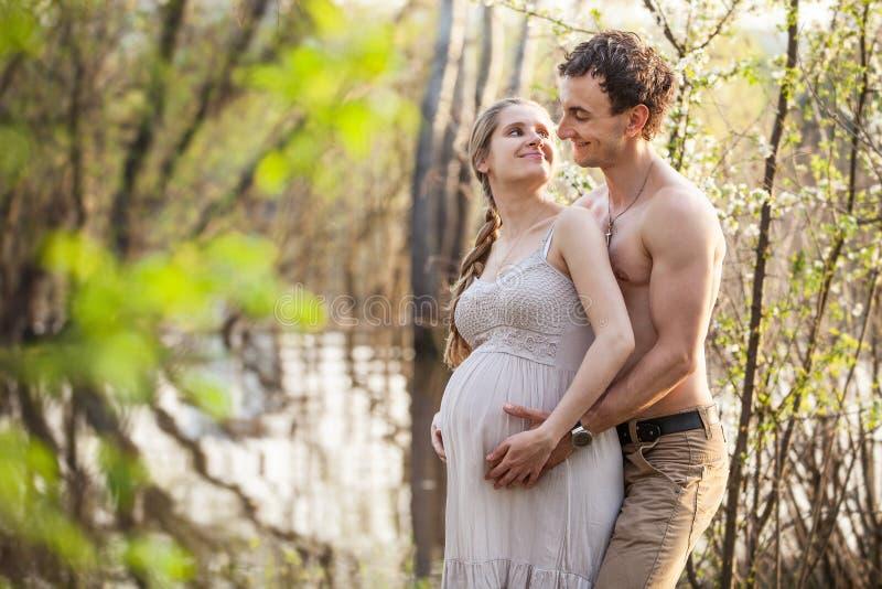 在河的年轻人怀孕的夫妇在春天 免版税库存图片