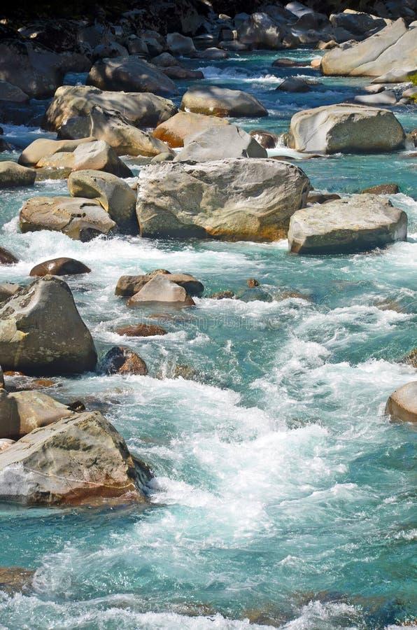 在河石之间的水急流 免版税图库摄影