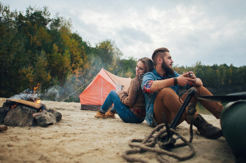 在河背景的逗人喜爱的年轻和愉快的夫妇 免版税库存图片