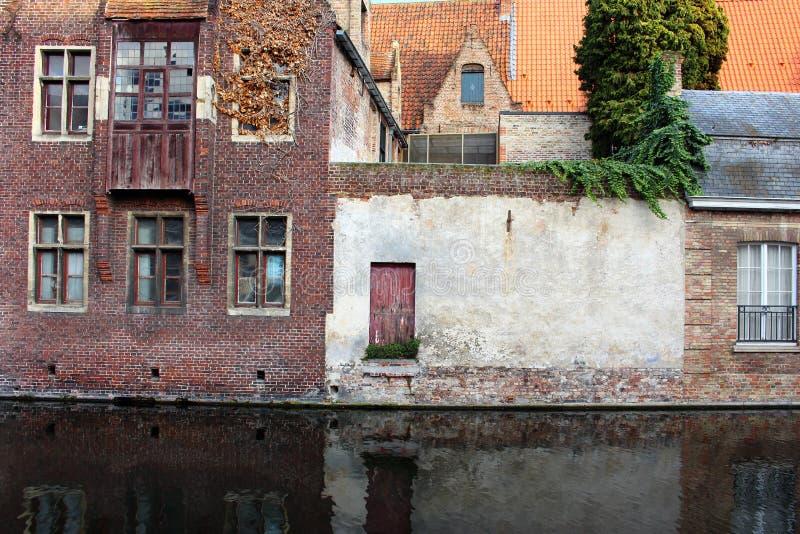 在河运河的中世纪大厦门面在老镇布鲁基布鲁日,比利时 有木门和窗口的葡萄酒房子 图库摄影