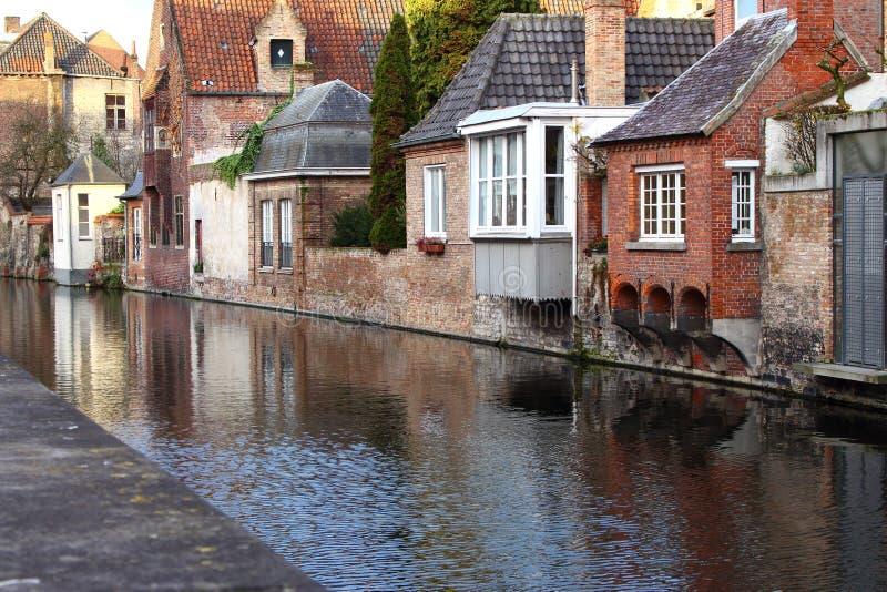 在河运河的中世纪大厦门面在老镇布鲁基布鲁日,比利时 有木门和窗口的葡萄酒房子 库存图片