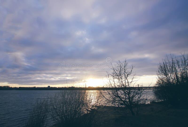 在河道加瓦河,里加,拉脱维亚的日落 都市风景在10月 免版税图库摄影