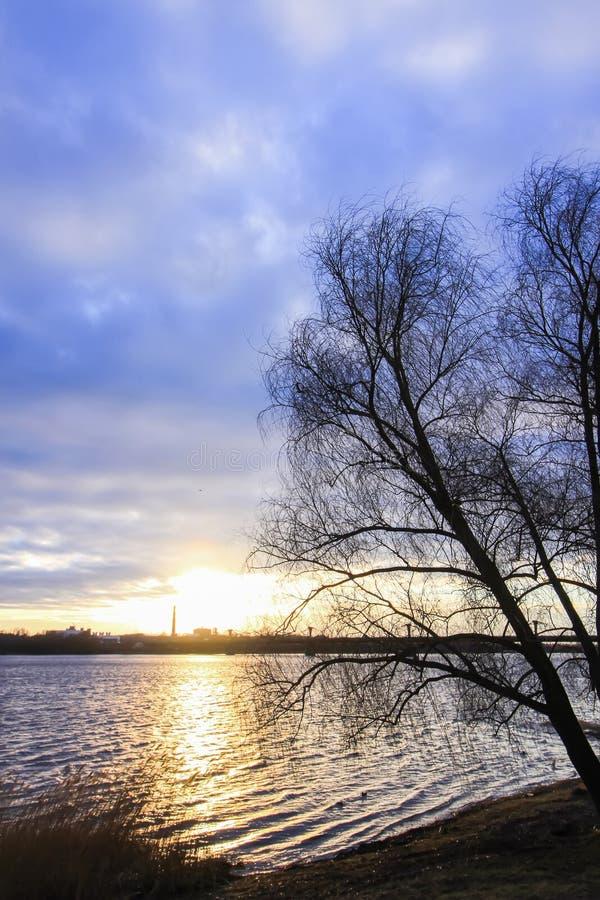 在河道加瓦河,里加,拉脱维亚的日落 都市风景在10月 免版税库存照片