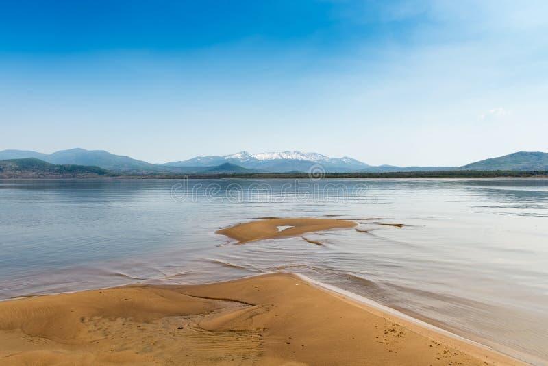 在河阿穆尔河的沙滩 黑龙江多雪的山的俄国远东美丽的银行的哈巴罗夫斯克地区和 免版税库存图片