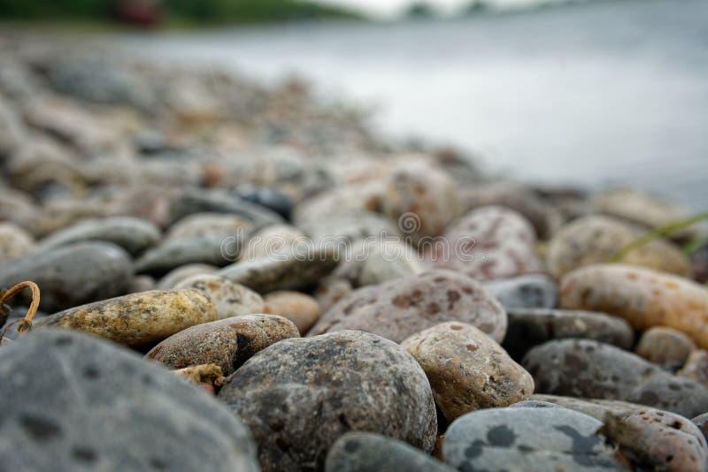 在河附近的五颜六色的海滩石头 免版税库存照片