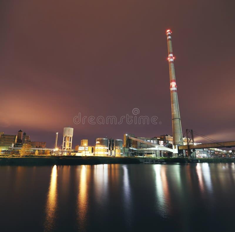 在河附近的化工工厂在晚上 免版税库存图片