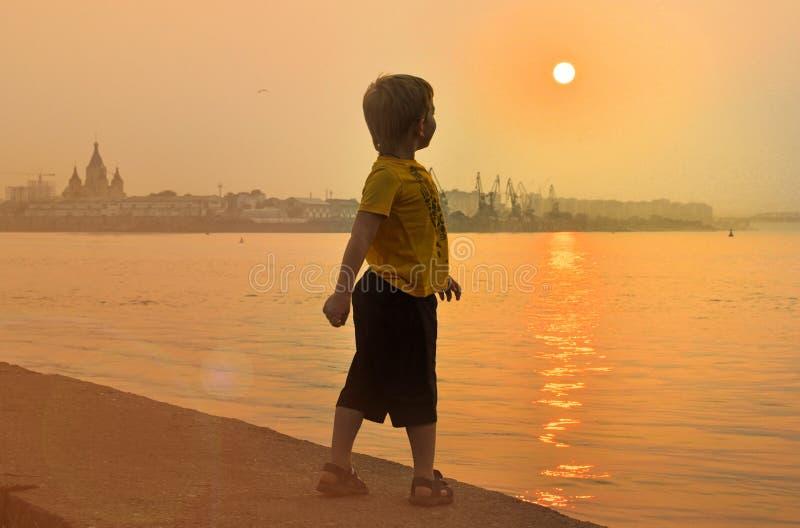 在河附近的男孩看美好的日落 免版税库存图片