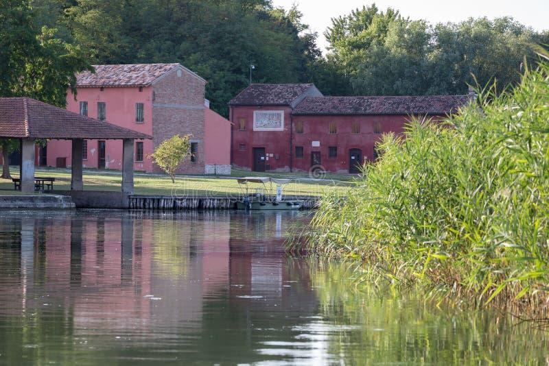 在河附近的红色农舍在与反射的绿色植被中在水中 库存照片