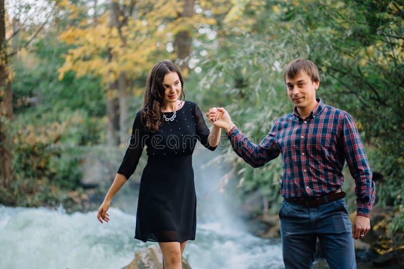 在河附近的美好的年轻夫妇 家庭价值观,爱,青年时期,幸福 免版税库存照片