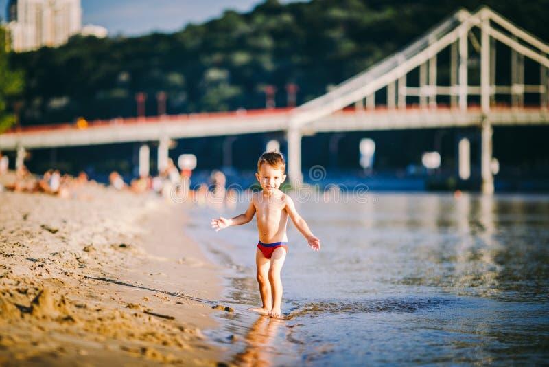 在河附近的题材夏天室外活动城市海滩的在基辅乌克兰 一点跑沿河的滑稽的男婴 免版税图库摄影