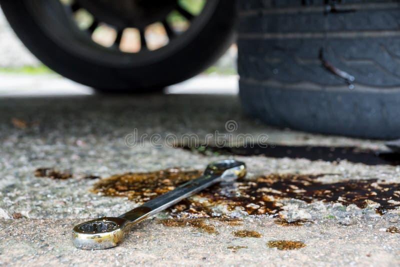 在油水池的一把套筒扳手与轮胎的 库存图片